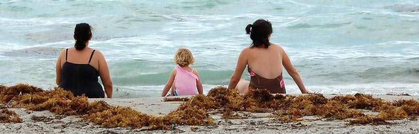 two-women-with-child-by-seashore
